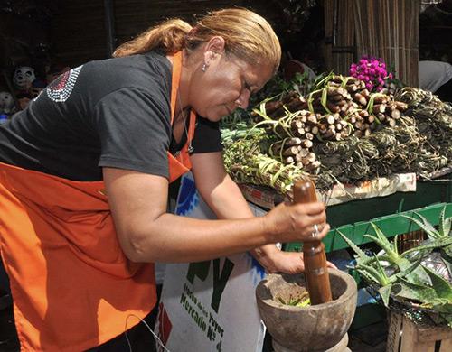 Zielarka ucierająca zioła do yerby wParagwaju
